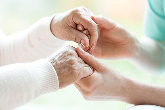 患者さんの手を握る看護師