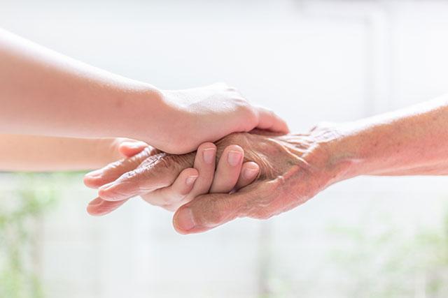 握手をする女性と老人の手