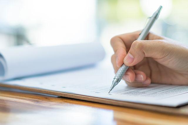 紙とペンを持つ手